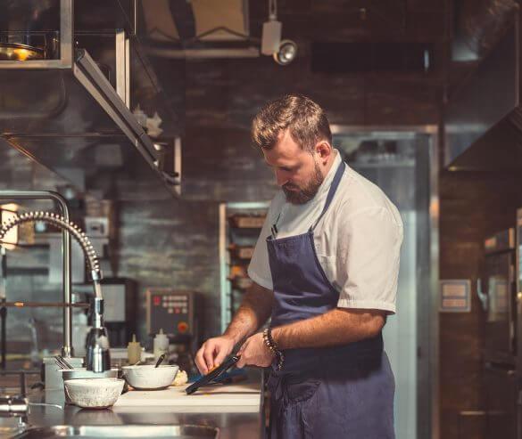 Młody kucharz gotuje w kuchni