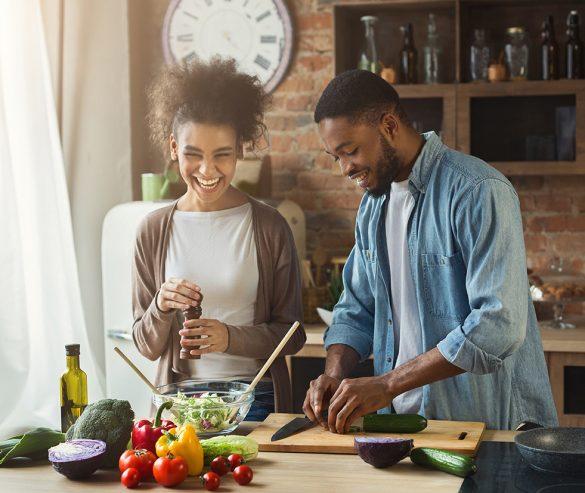 Śmiejąc się czarna para razem przygotowuje zdrową sałatkę w kuchni na poddaszu. Młody rodzinny obiad do gotowania